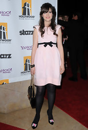 Zooey Deschanel was a pastel princess in a pale pink frock with pronounced cap sleeves and a darling black bow belt.
