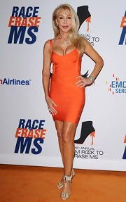 Linda Thompson showed off her toned and tanned body in a sexy orange bandage dress.
