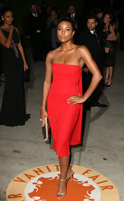 Gabrielle paired a fabulously form fitting red dress with strappy gold stilettos.