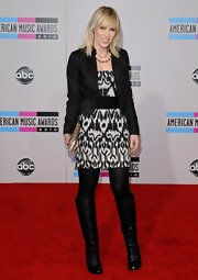 Natasha Bedingfield hit the red carpet in black knee high boots. The songstress paired the leather boots with a black and white print dress and fitted black jacket.