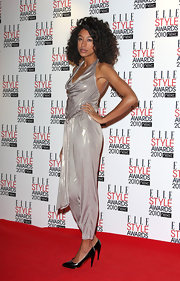Corinne looked glamorous in a metallic halter jumpsuit with free-flowing curls and patent pumps.