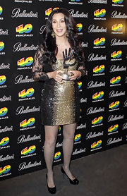 Cher wore a sequined cocktail dress with sheer lace sleeves for this red carpet look.