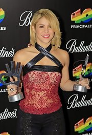 Shakira new cropped 'do showed off the unique leather straps of her sheer red halter top.