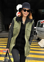 Jessica wore a unique dress hat for her trip to the airport. She paired her cap with an army green and leather jacket.