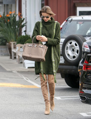 Alessandra Ambrosio showed off her edgy winter style in a green Concepto turtleneck dress accented with two vertical belts.