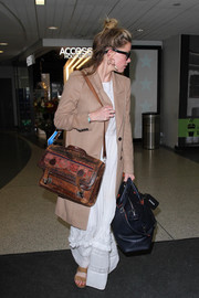 Amber Heard was spotted at LAX wearing a tan wool coat over a white maxi dress.