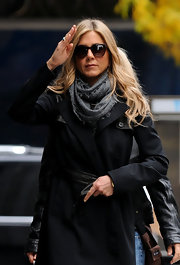 Aniston's black trenchcoat looked casual yet cool with leather detailing, adding some modern flare to a classic piece.