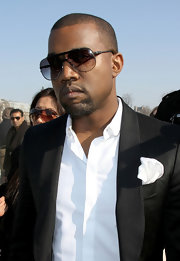 Kanye West paired his chic blazer and button down shirt with classic aviator shades. You can always count on West to arrive in style!