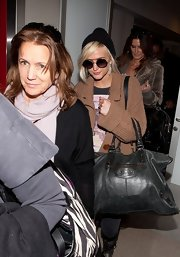 Ashlee Simpson stashed her airport essentials in a black leather Balenciaga bag.