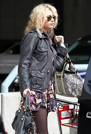 Aly paired her floral print dress with a cool leather jacket while hitting the airport.