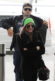 Avril wears a black wool coat with her green beanie and shades for a trip to the airport.