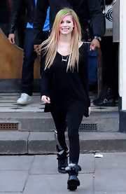 Avril opts for a long-sleeved black tee over her metallic striped leggings and combat boots.