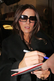 Kate's chic oversized square sunglasses have gradient lenses and a black plastic frame. This is a great shape for her face and they look very stylish with her wool trench coat.