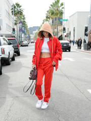 Bella Hadid matched her jacket with a pair of red track pants.
