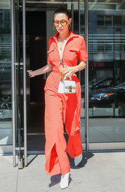 Bella Hadid cut a chic figure on the streets of New York City in a plunging red jumpsuit with a cinched-in waist and split legs.