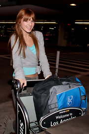 Bella looks darling in a gray wrap sweater top over a vibrant cami at the airport.