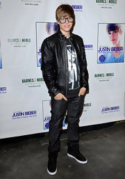 Justin wears a long pendant necklace over his graphic tee and leather jacket at his book signing.