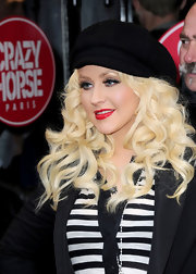 Christina wears a black knit newsboy cap for this casual red carpet ensemble.
