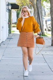 Busy Philipps teamed her sweater with an ochre button-front mini.