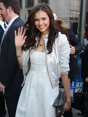 Nina is carrying a soft silver metallic clutch that looks great with her white dress.