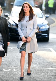 Kate Middleton stepped out in Kensington wearing a baby-blue maternity coat by Seraphine.