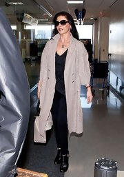 Catherine Zeta Jones dressed up her airport look with a long wool coat with cutout designs.