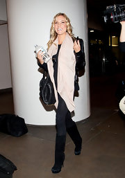 K. Cav traveled in style at LAX. She paired her chic skinny jeans with black suede platform boots.