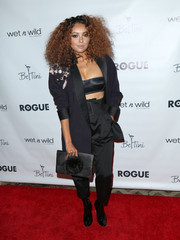 Kat Graham accessorized her outfit with a pompom-embellished satin clutch.