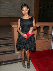 Jada Pinkett Smith accessorized with a red satin clutch for a spot of color to her dark outfit.