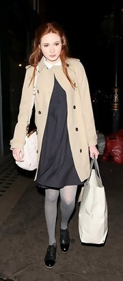 Karen Gillan kept her style classic wearing a tan double-breasted pea coat over a navy frock.