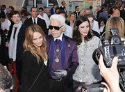 Karl paired his purple suit with a pendant necklace.