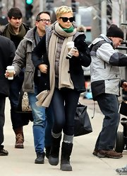 Charlize Theron bundled up in a black down jacket while on set in Boston.