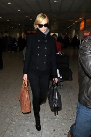 Charlize Theron attempted to go incognito at Heathrow airport in a sophisticated black military style jacket.