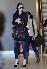 "Charlize carries the functional-chic ""Saddle Bag"" to fit all of her travel needs."