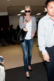 Charlize Theron traveled in style in a gray cardigan paired with distressed skinny jeans.