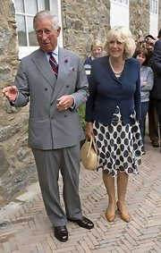 Camilla keeps a summery polka-dot dress more modest by layering over a fitted blazer in a corresponding color.