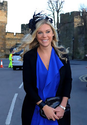 Chelsy Davy wore a black decorative hat featuring plumes of feathers and a rose to a wedding.