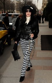 Cher was out and about in Paris carrying a black crocodile clutch and wearing an eye-catching pair of harlequin pants.