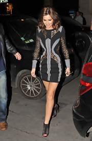 "Cheryl stepped out in a bold lace inset mini dress paired with sexy peep-toed black ""Elastic Sandals"". The $880 heels showed off her vibrant pedicure and complemented the style of her panneled ensemble."