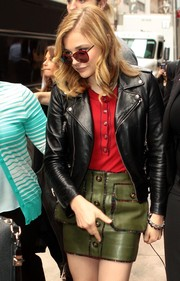 Chloe Grace Moretz was spotted leaving the Sirius XM radio studios looking cute and edgy in an olive-green leather mini and a biker jacket.