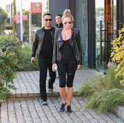 Chrissy Teigen pairs athletic wear with a black moto jacket while stepping out with hubby John Legend.