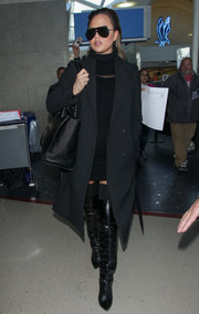 Chrissy Teigen layered a black wool coat over a sheer-panel turtleneck dress for a flight.
