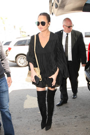 Chrissy Teigen hovered between boho and goth in a tiered black peasant dress while catching a flight out of LAX.