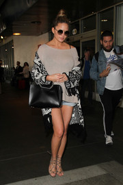Chrissy Teigen finished off her airport outfit with a fringed black-and-white cardigan.