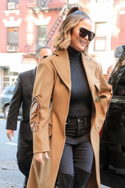Chrissy Teigen stepped on in New York City wearing a pair of shield sunglasses by Saint Laurent.