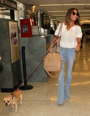 Chrissy Teigen covered up her sexy stems in a pair of faded blue bootcut jeans by Frame Denim.