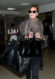 One bag was obviously not enough for the gorgeous traveler as she also lugged a much bigger but just as chic black snakeskin tote.