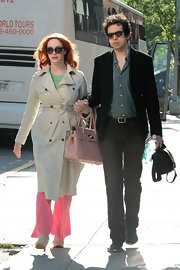 Christina Hendricks looked classic in a khaki trench and pink slacks while out for a walk.