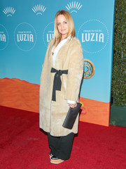 Mena Suvari paired her chic coat with a black satin clutch.