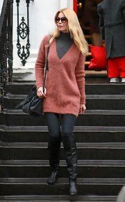 Claudia wears an angora v-neck sweater in a delightful coral hue.